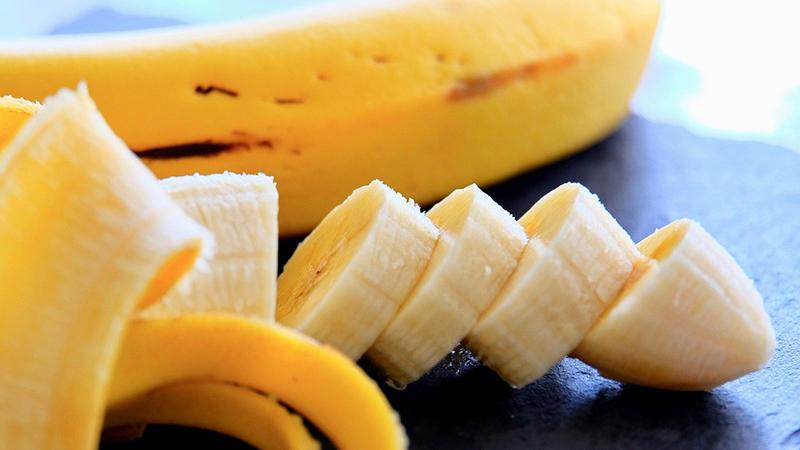 An unpeeled and a peeled banana.