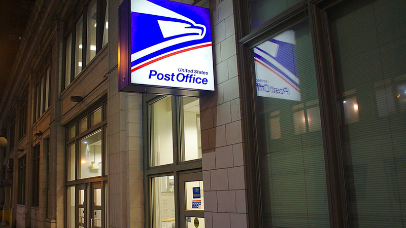 A United States Post Office sign by the entrance