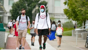 Masked students walk between Strong and Glass halls.