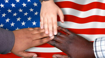 Three different colored hands on an American flag.