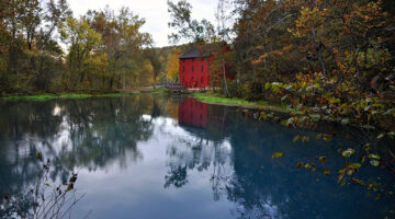 Ozarks scenery: a red building by a lake surrounded with trees.