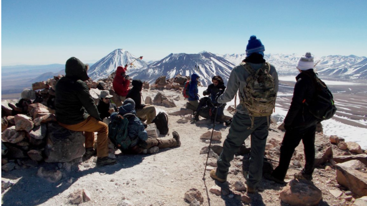 Undergraduate students from the 2017 Chile Volcanology Study Away at the top of the Cerro Toco volcano in northern Chile. Juriques and Licancabur volcanoes can be seen in the back and are a focus of the project.