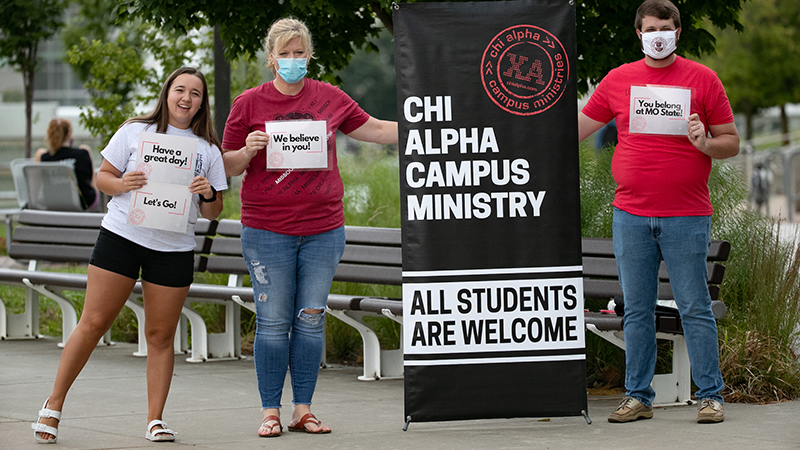 Two female students and a male student post next to a Chi Alpha Campus Ministry standing banner on the Missouri State University campus.