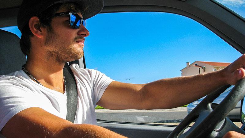 A man inside a car driving.