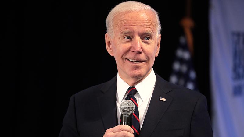 President-elect Joe Biden holds a microphone.