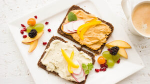 A healthy breakfast of hummus on whole wheat bread with assorted fruits.