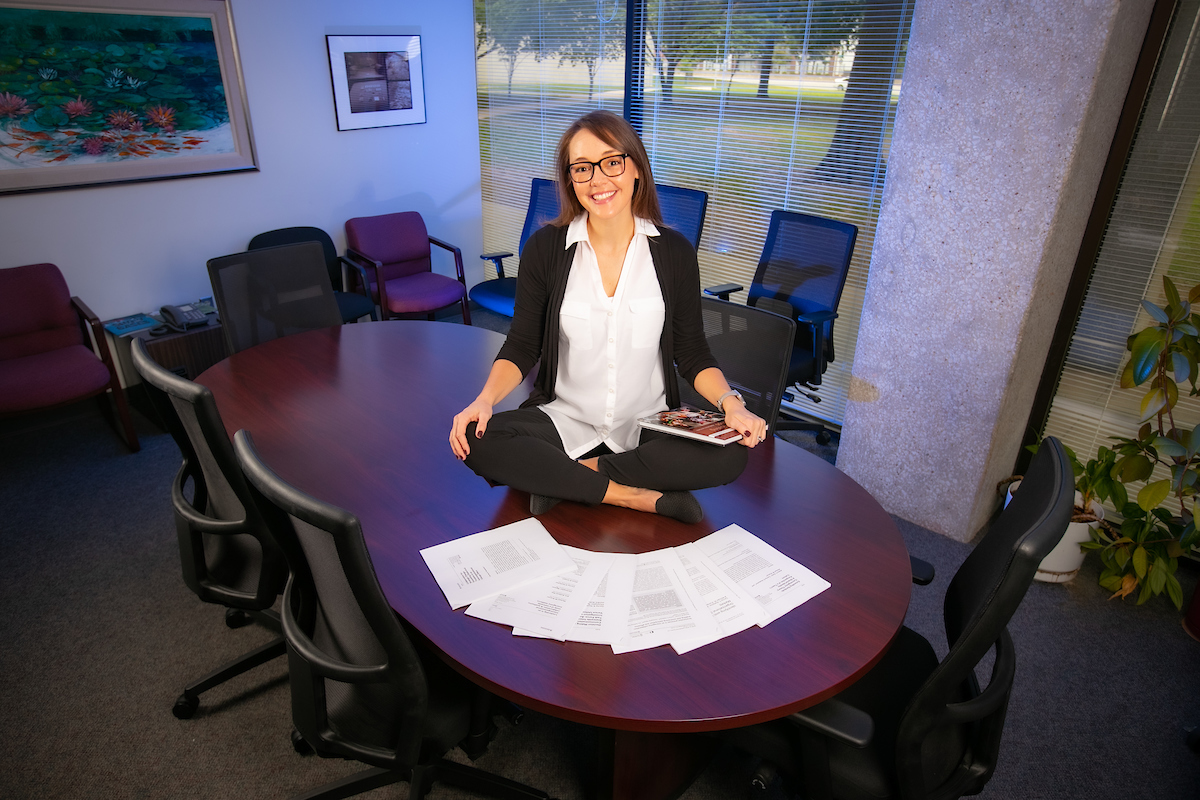 Dr. Carrisa Hoelscher sits on conference table surrounded by her research articles.