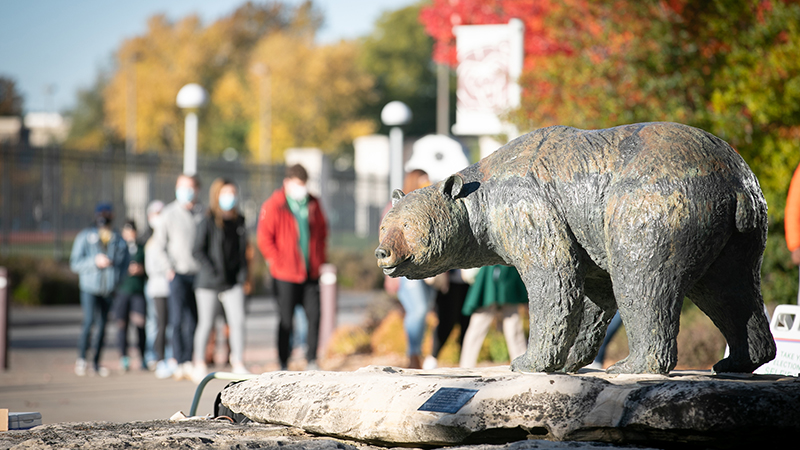 Students walk by a Bear statue on the Missouri State University campus.