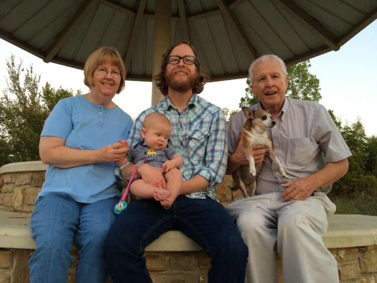 Three people pose with a baby and a dog