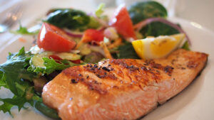 A plate of salmon with a side of salad.
