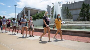 Students and families walk by the John Q. Hammons Fountains on a warm, sunny, summer day.
