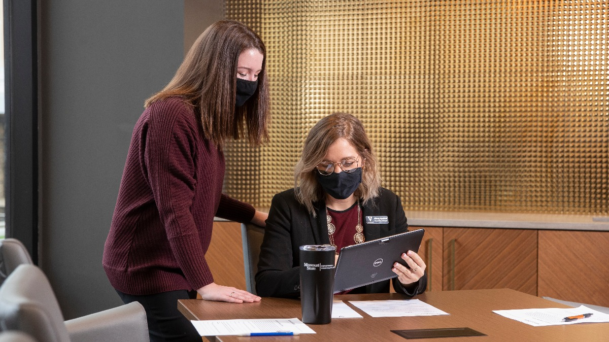 Two masked employees examine work on a tablet screen together.