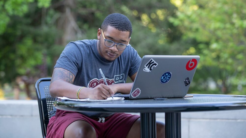 A student studies on campus outside with a laptop.