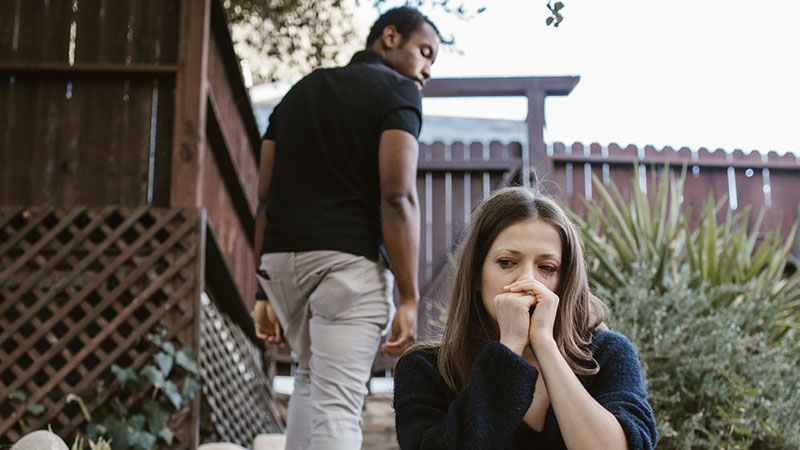 A Black man walking away from a dejected looking Caucasian woman.