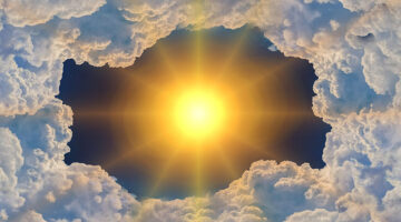 The sun shining brightly through the clouds.