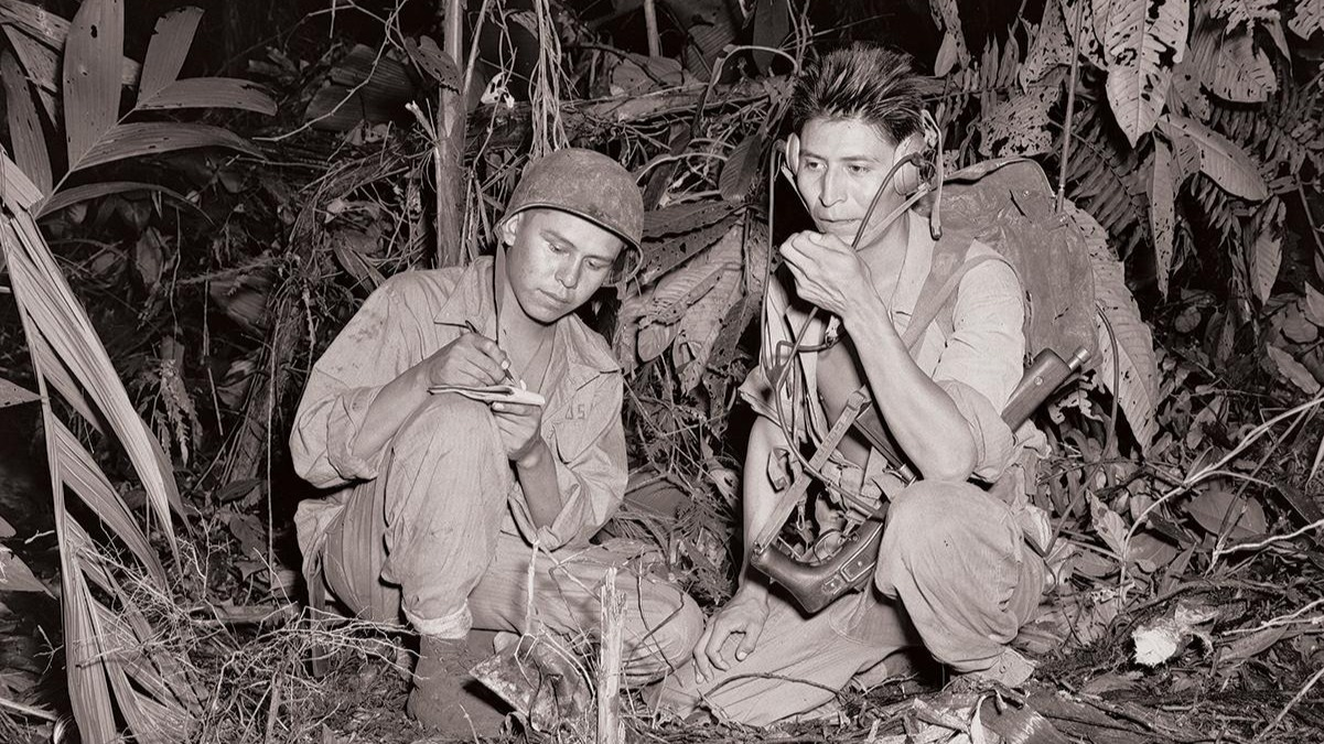 Navajo code talkers Corporal Henry Bahe Jr. (left) and Private First Class George H. Kirk (right) transmit over a portable radio in Bougainville in the South Pacific during December 1943.