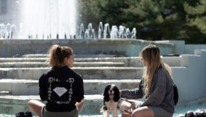 Two girls and a small dog sitting on the ledge of the fountain.