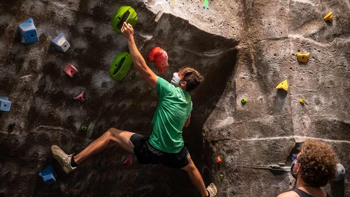 Student climbs rock wall in Foster Recreation Center.Student climbs rock wall in Foster Recreation Center.