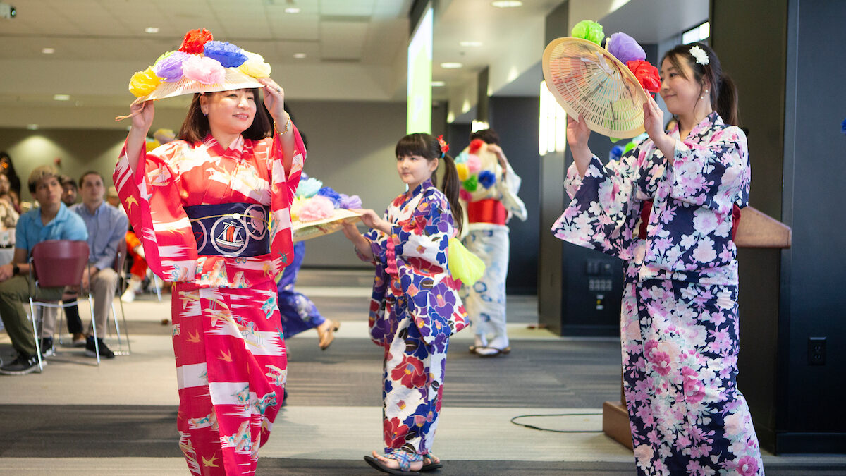 Three women in traditional Asian dresses dancing.