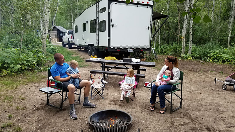 A family with young kids sitting around a campfire.