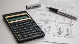 A calculator, financial statement and pen.