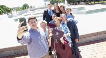 A family poses for a photo with their Missouri State graduate at the John Q. Hammons Fountain.