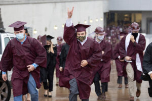 Students run through the rain after the fall 2020 commencement ceremony