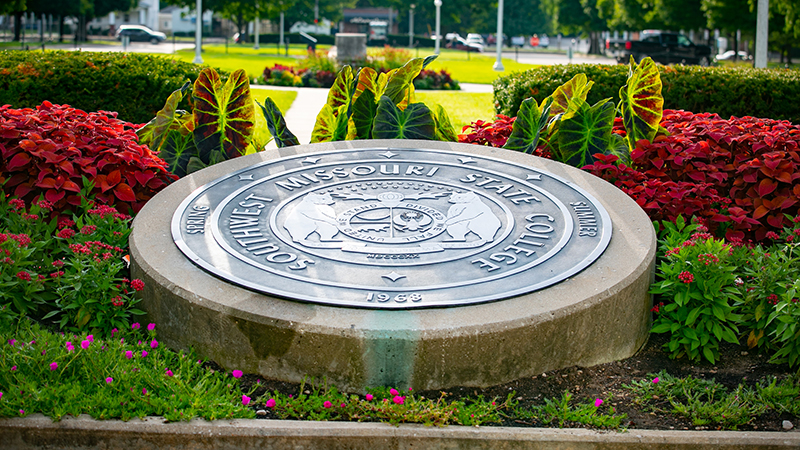 The university seal surrounded by colorful flowers.