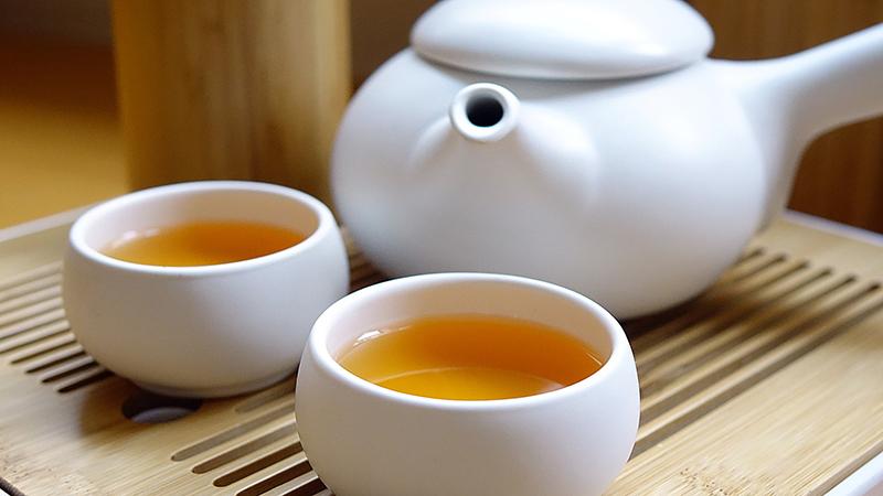 A white porcelain teapot with two cups filled with tea.