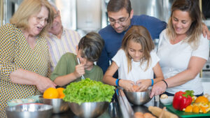 A family cooks together in the kitchen.