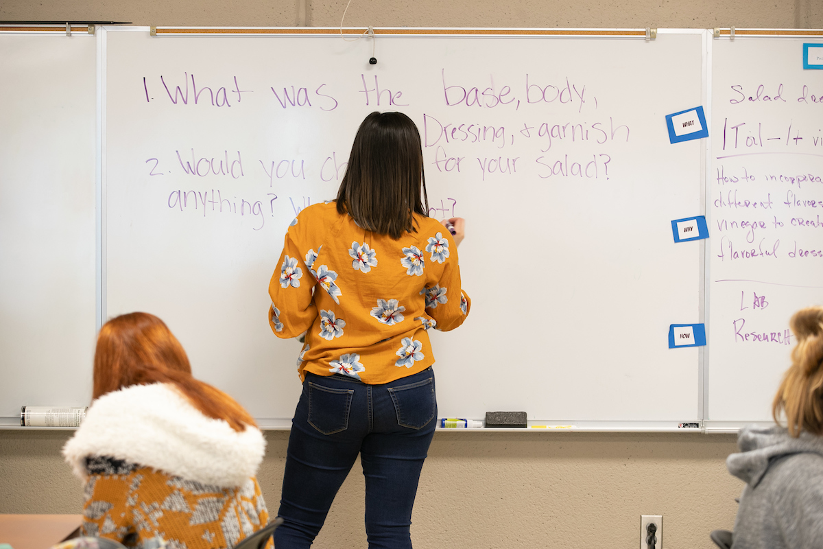 Teacher writes on white board in front of classroom.
