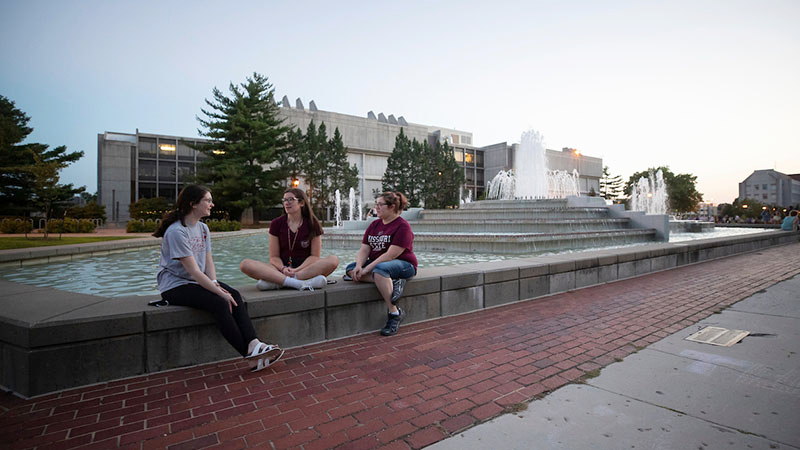 Students relax by the John Q. Hammons Fountains on campus.