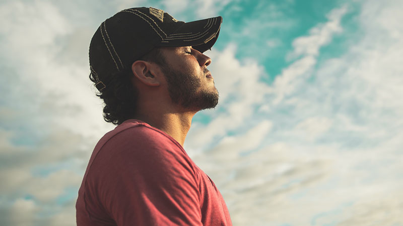 A man looks to the sky with his eyes closed.