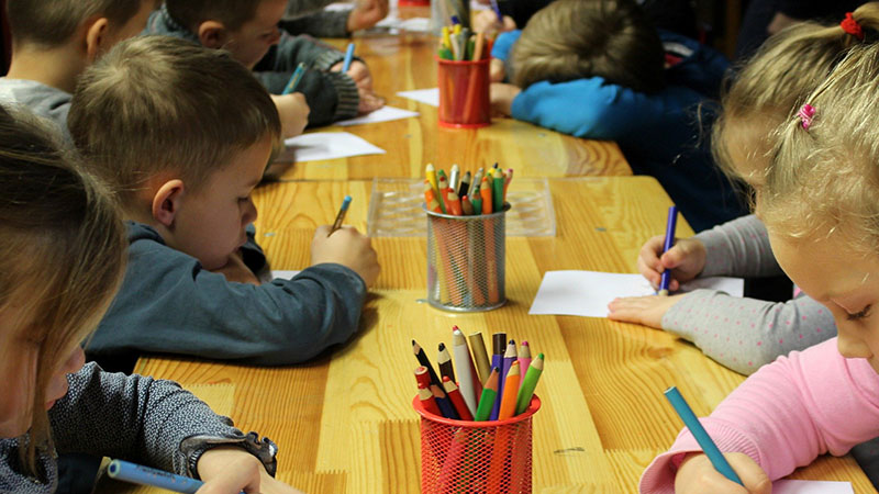 A group of kids sitting at a table writing and drawing.