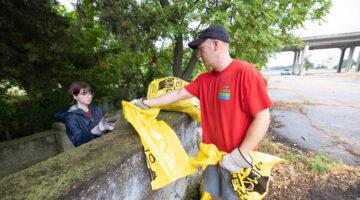 Matt Pierson hands trash bag to female student at Jordan Creek.