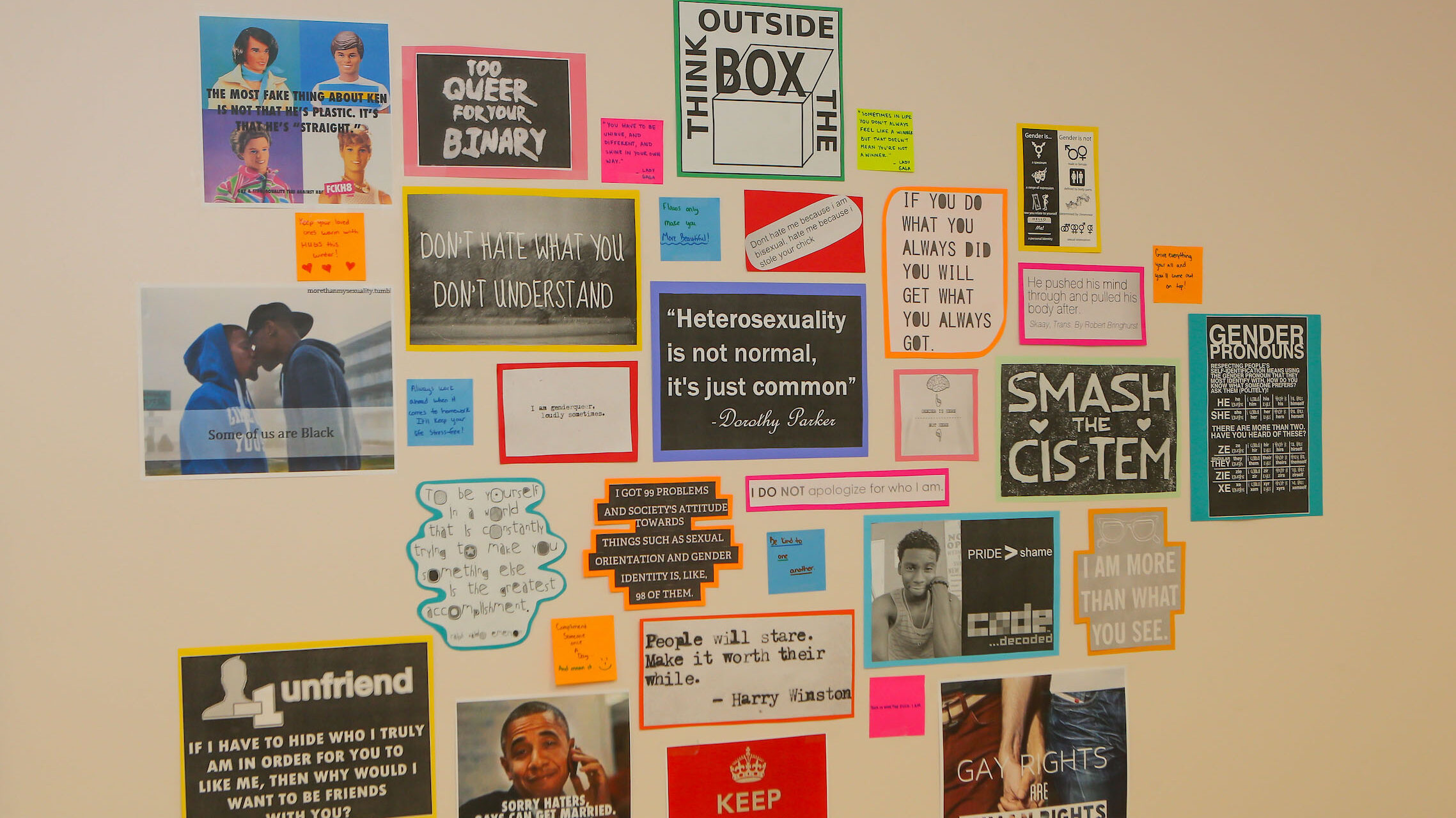 Various quotes about LGBTQ+ on a wall.
