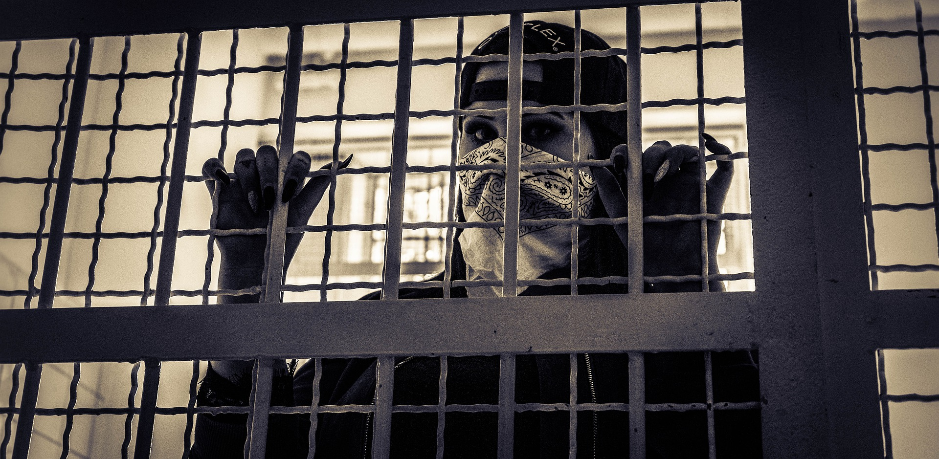 A woman behind bars in jail.