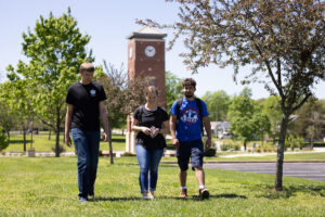 Three students walk across West Plains' campus grounds.