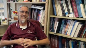 Dr. Gary Meints sits in his office surrounded by chemistry books as learning material.